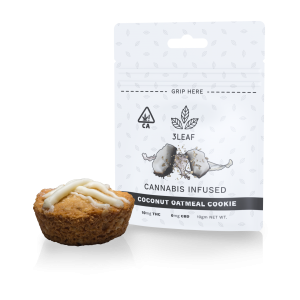 3Leaf natural Coconut Oatmeal Cookie. One cookie, drizzled with white chocolate, is placed in front of a 3Leaf package.