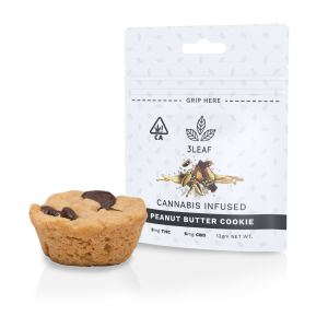 3Leaf ratio-infused Peanut Butter Cookie. One peanut butter cookie with chocolate chips is placed in front of the 3Leaf package.