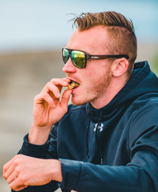 Man eating a recreational edible after a hike. This edible is a peanut butter ratio-infused cookie from 3Leaf Edibles.