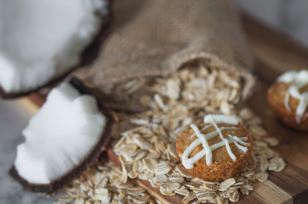 3Leaf Coconut Oatmeal Cookie is placed on top of natural ingredients like rolled oats and chunks of coconut.
