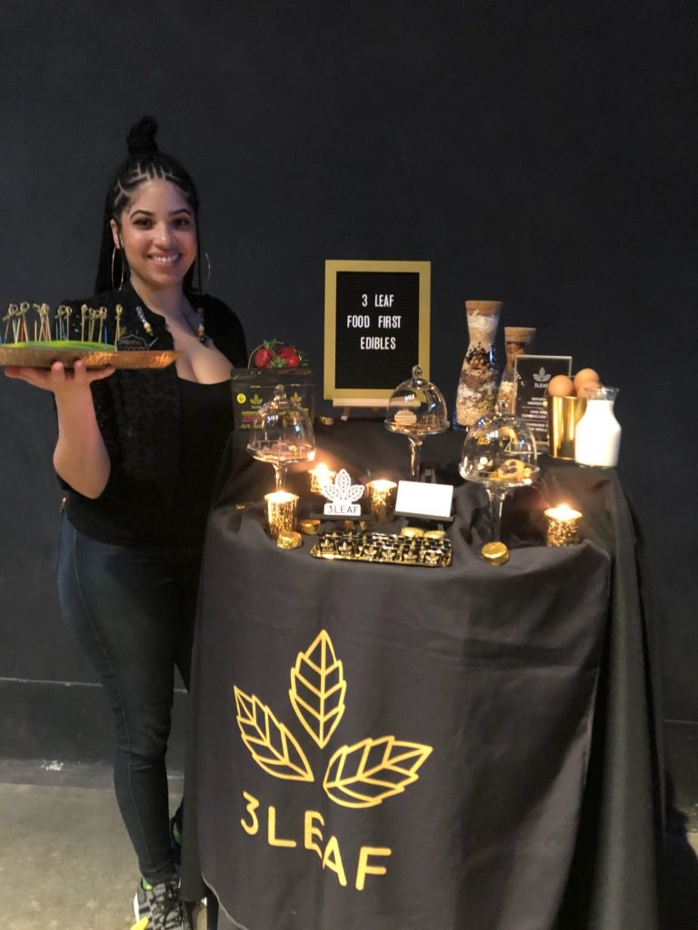 A 3Leaf team member hands out samples of edibles at an event.