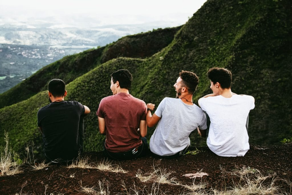 Four men sitting at the edge of a mountain, laughing